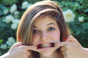 Teenage girl makes a funny face with braces on