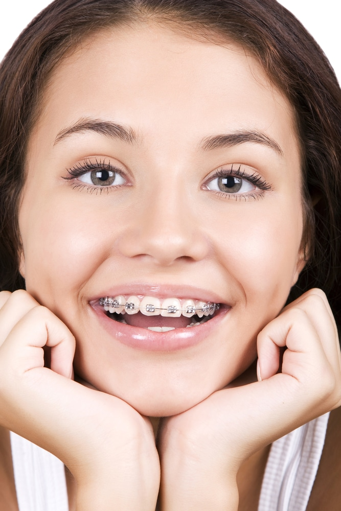 Photo of a pretty young girl smiling with braces on.