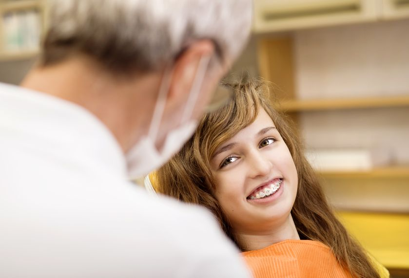 Young Girl Smiling in Orthodontists Office chair
