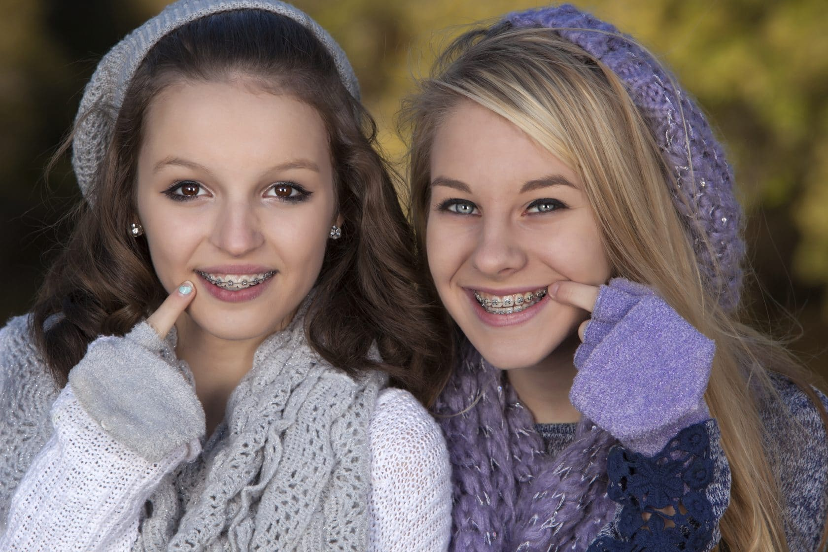 Two teenage girls smiling as they point to their braces