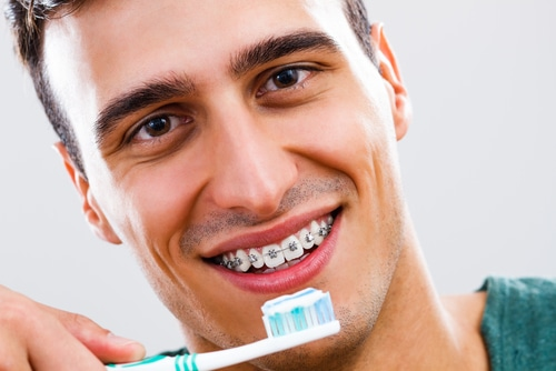 Man with braces uses toothbrush