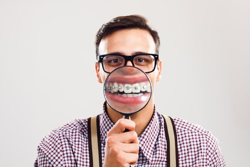 Man in braces with orthodontic braces holding magnifying glass