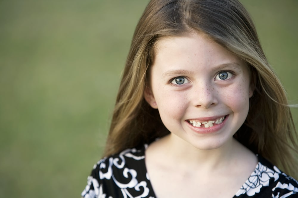 Young girl with crooked teeth smiling