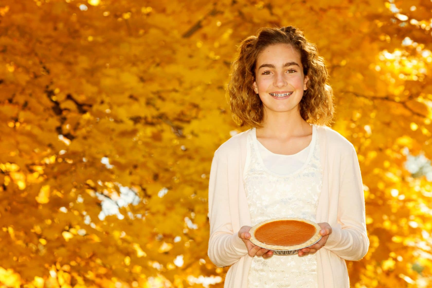 Girl with braces holding a pie on Thanksgiving.