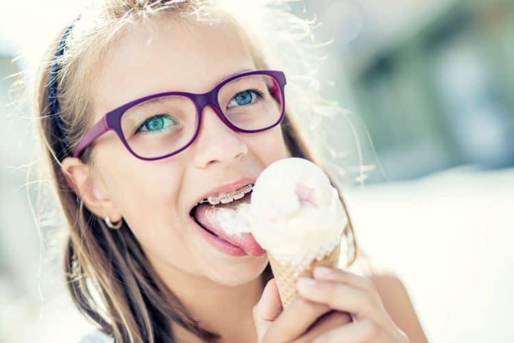 Young girl with braces eating braces-friendly ice cream